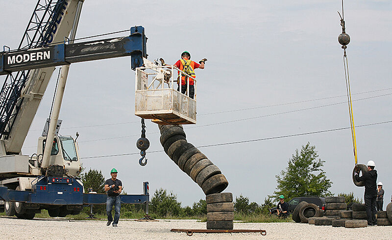 A construction worker on the ground and one in a crane with a tire sculpture.