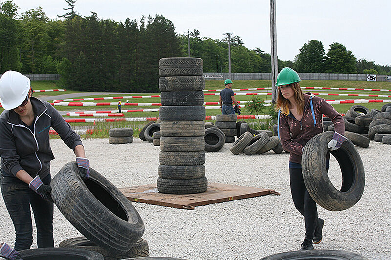 Two women carry tires for an outdoor sculpture.