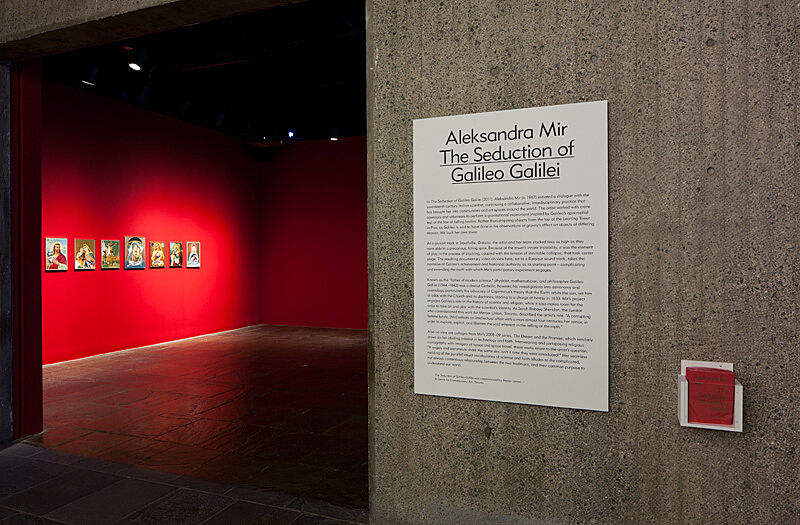 A view of a gallery installation with a piece of paper on the wall.