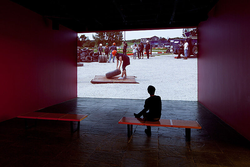 A person sits on a red bench in a gallery watching a video.