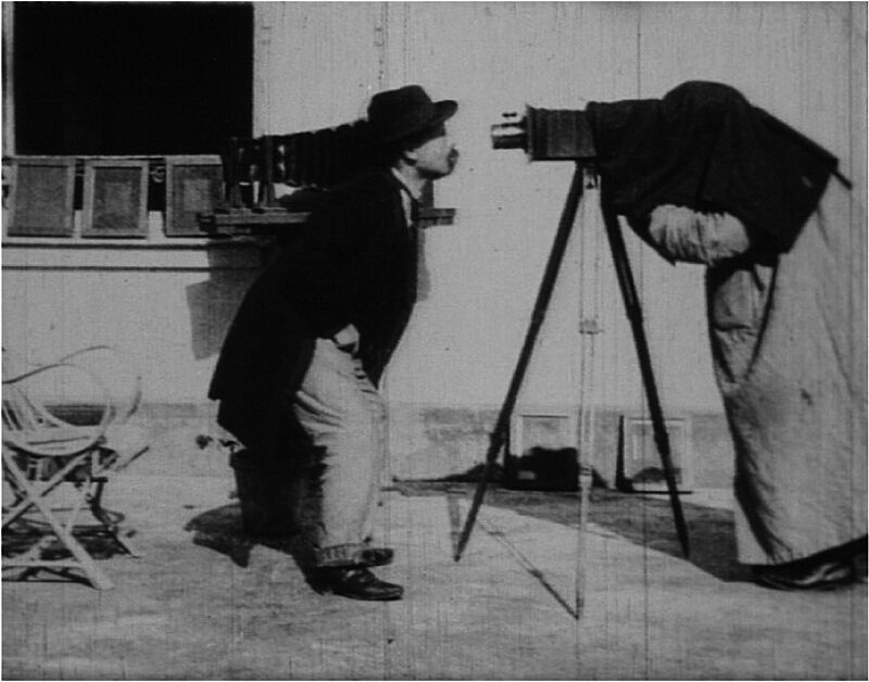 A man stands in front of a film camera.