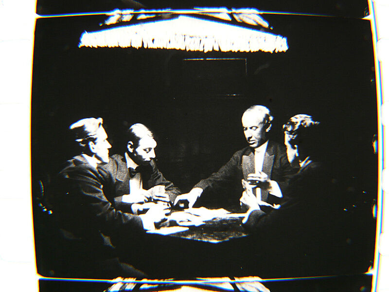 Four men play cards in a black and white film still.