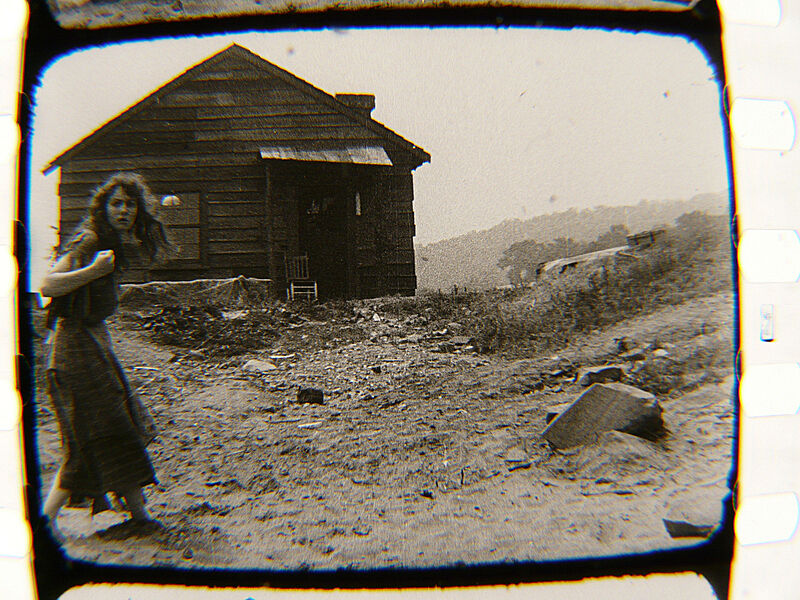 A woman stands in front of a cabin.