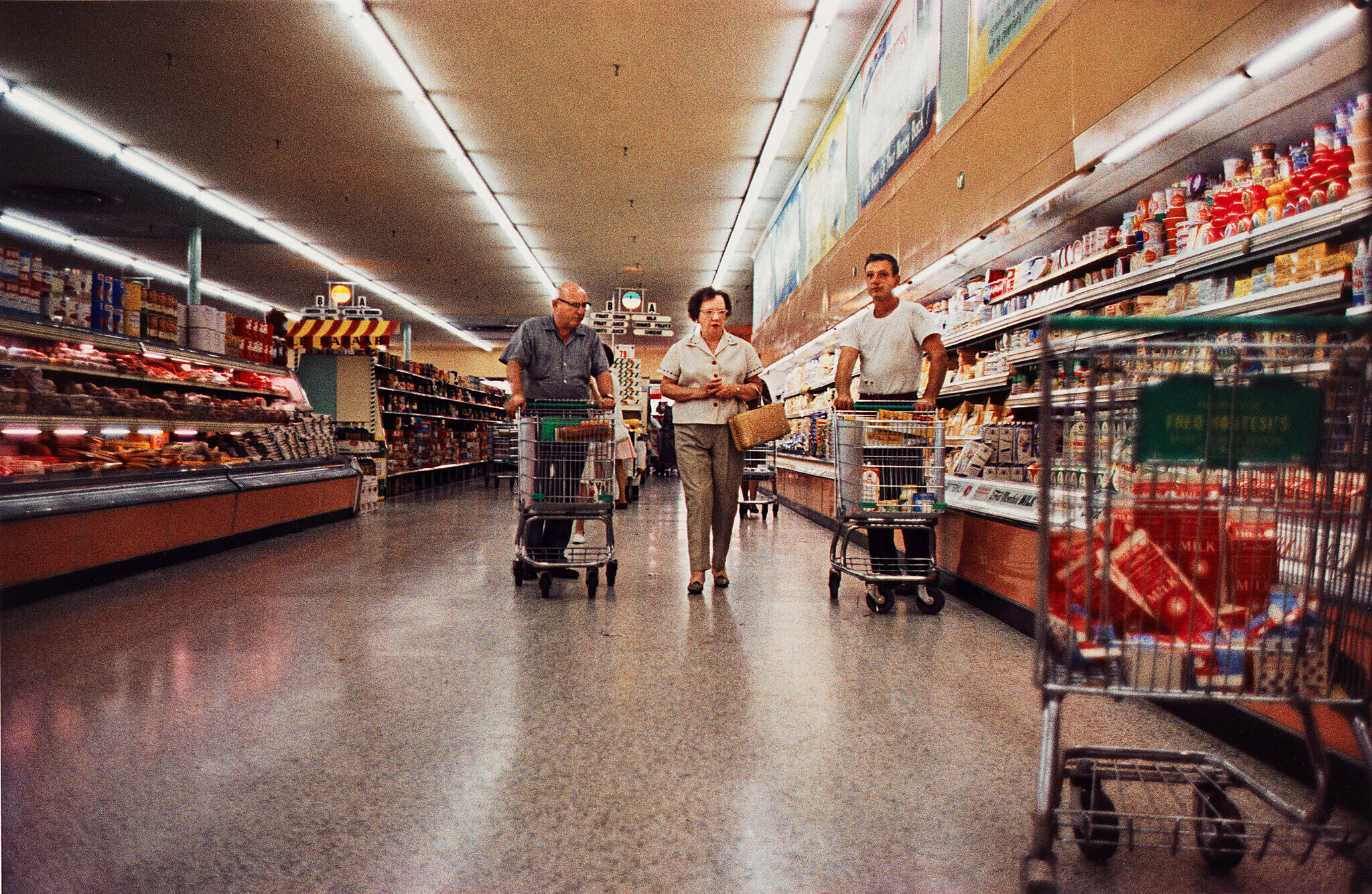 Three people in a supermarket aisle.