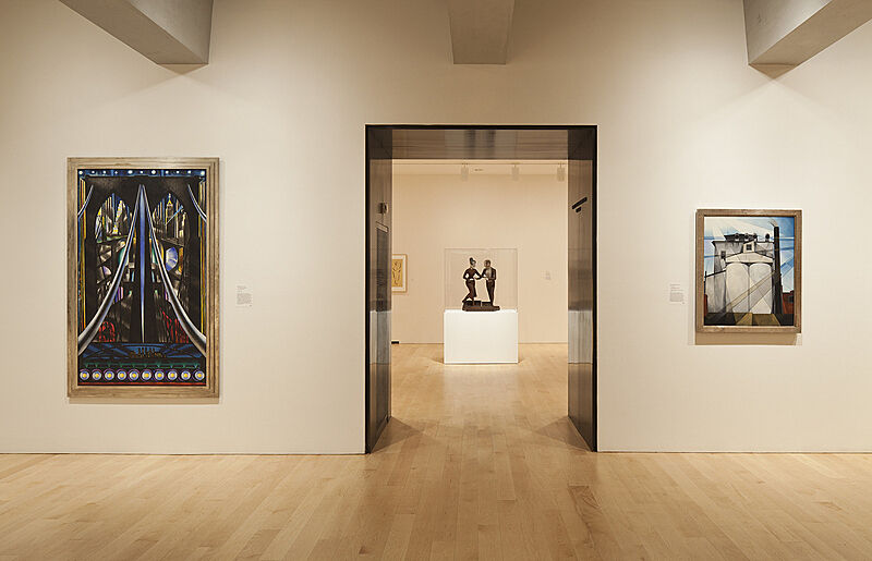 A sculpture through a door and two paintings on the wall.
