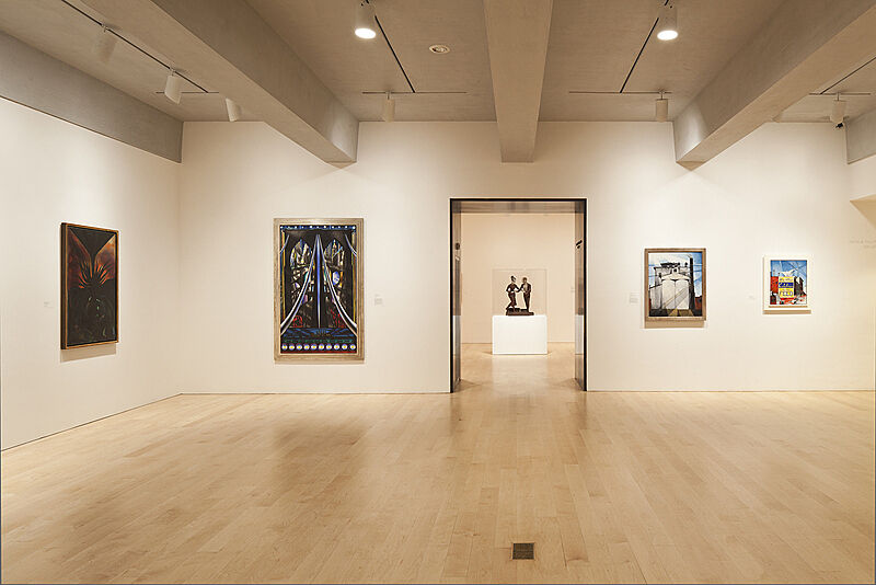 Paintings on the walls of a gallery with a sculpture through a door in another gallery.