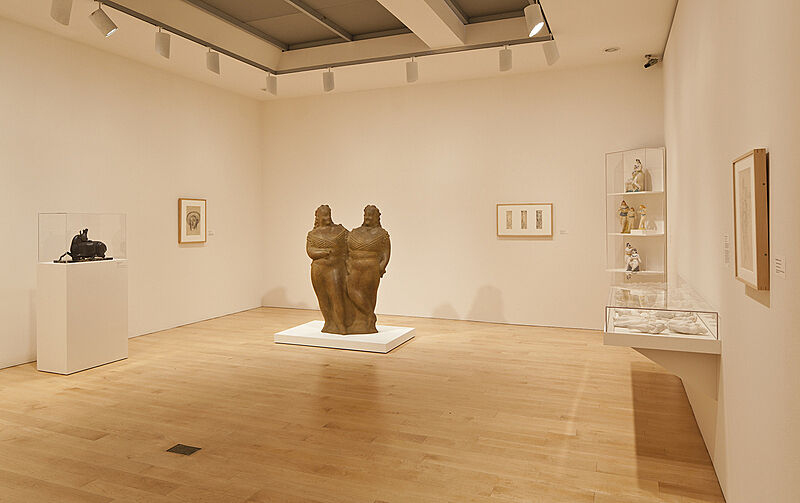 Sculptures and paintings in an art gallery with white walls.