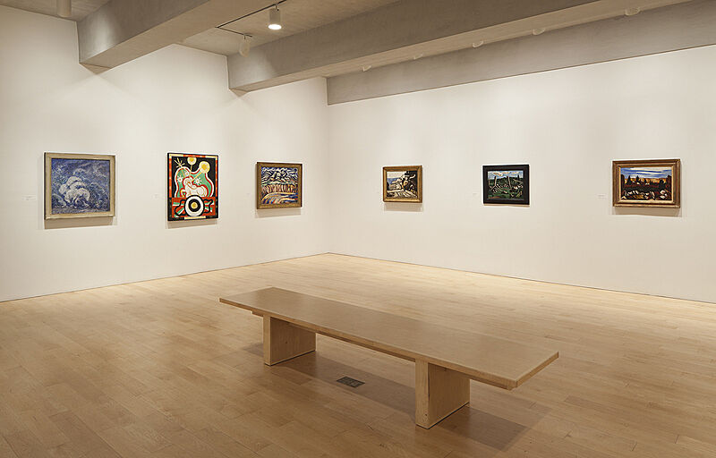 A bench in an art gallery with paintings on the wall.