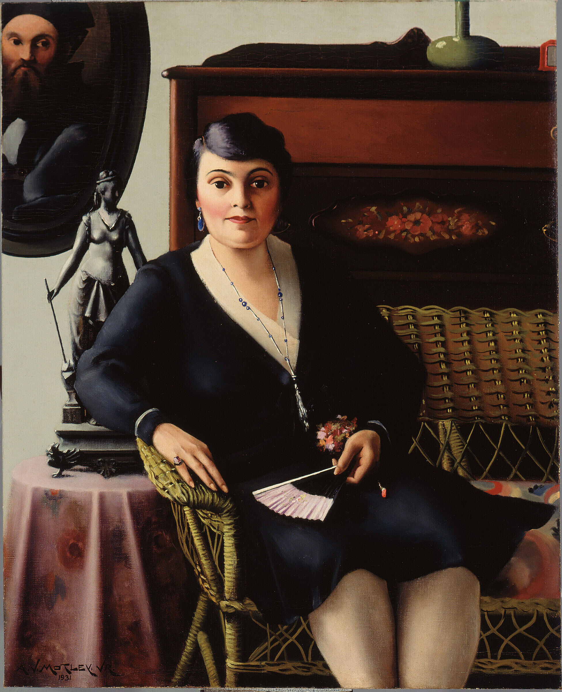 A woman in a black dress sits on a wicker chair.