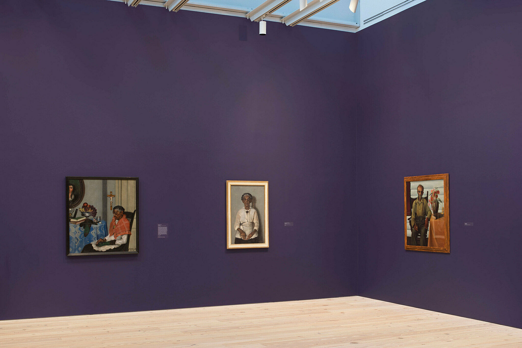Three paintings in a gallery with purple walls.
