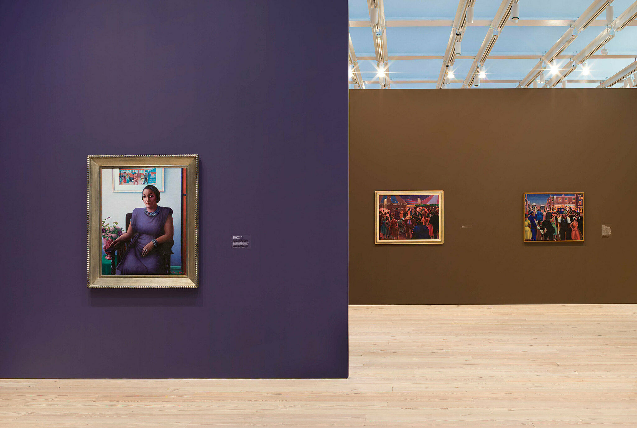 Paintings by Archibald Motley in a gallery with purple and brown walls.