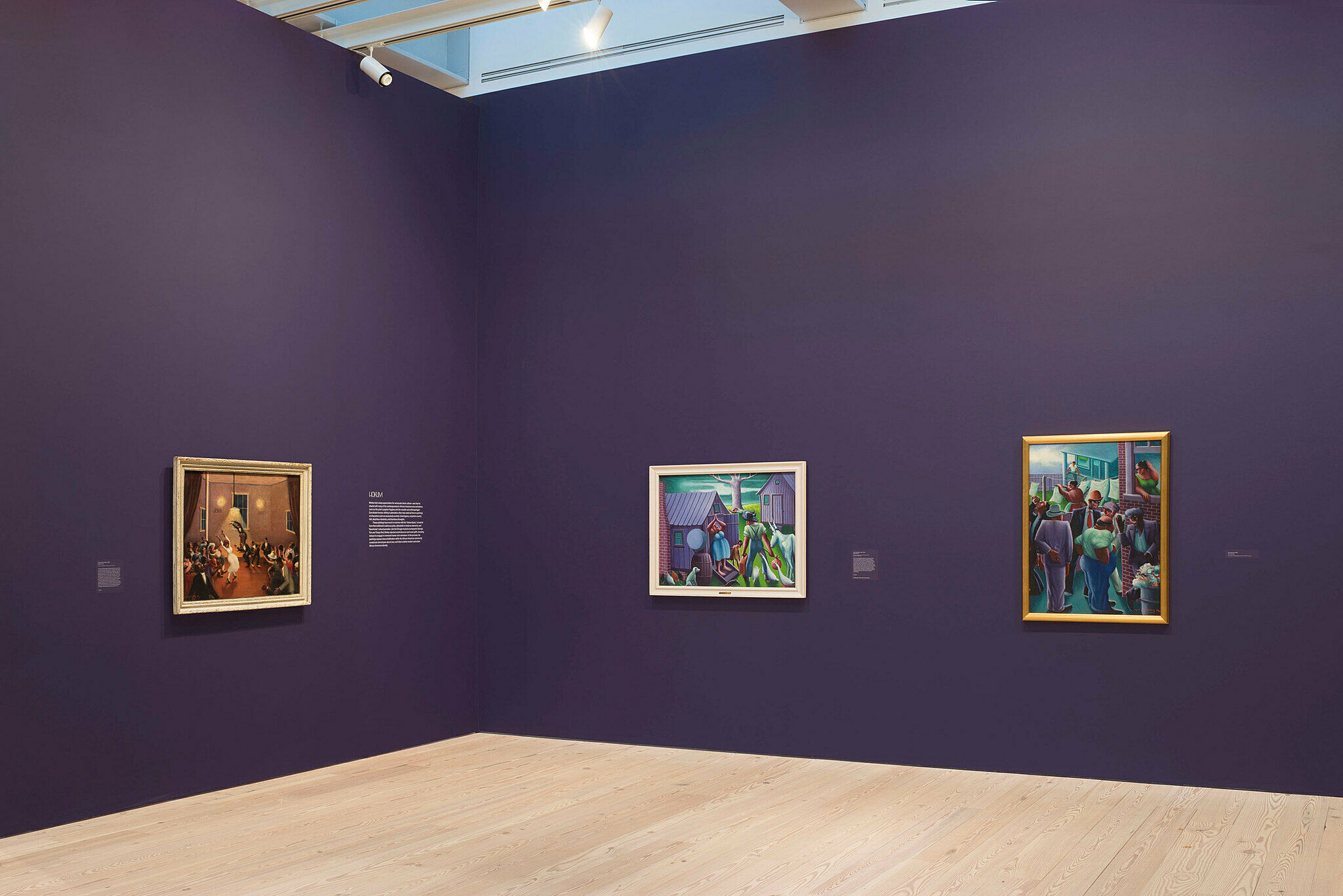 Three paintings by Archibald Motley in a gallery.