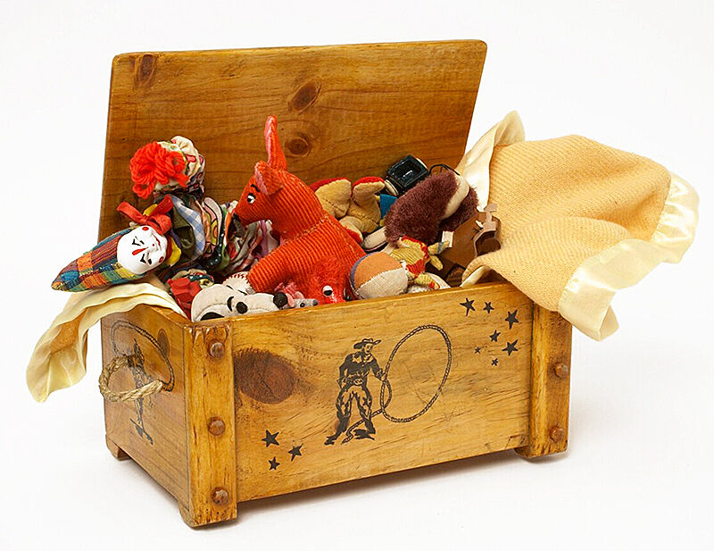 A wooden chest filled with toys.