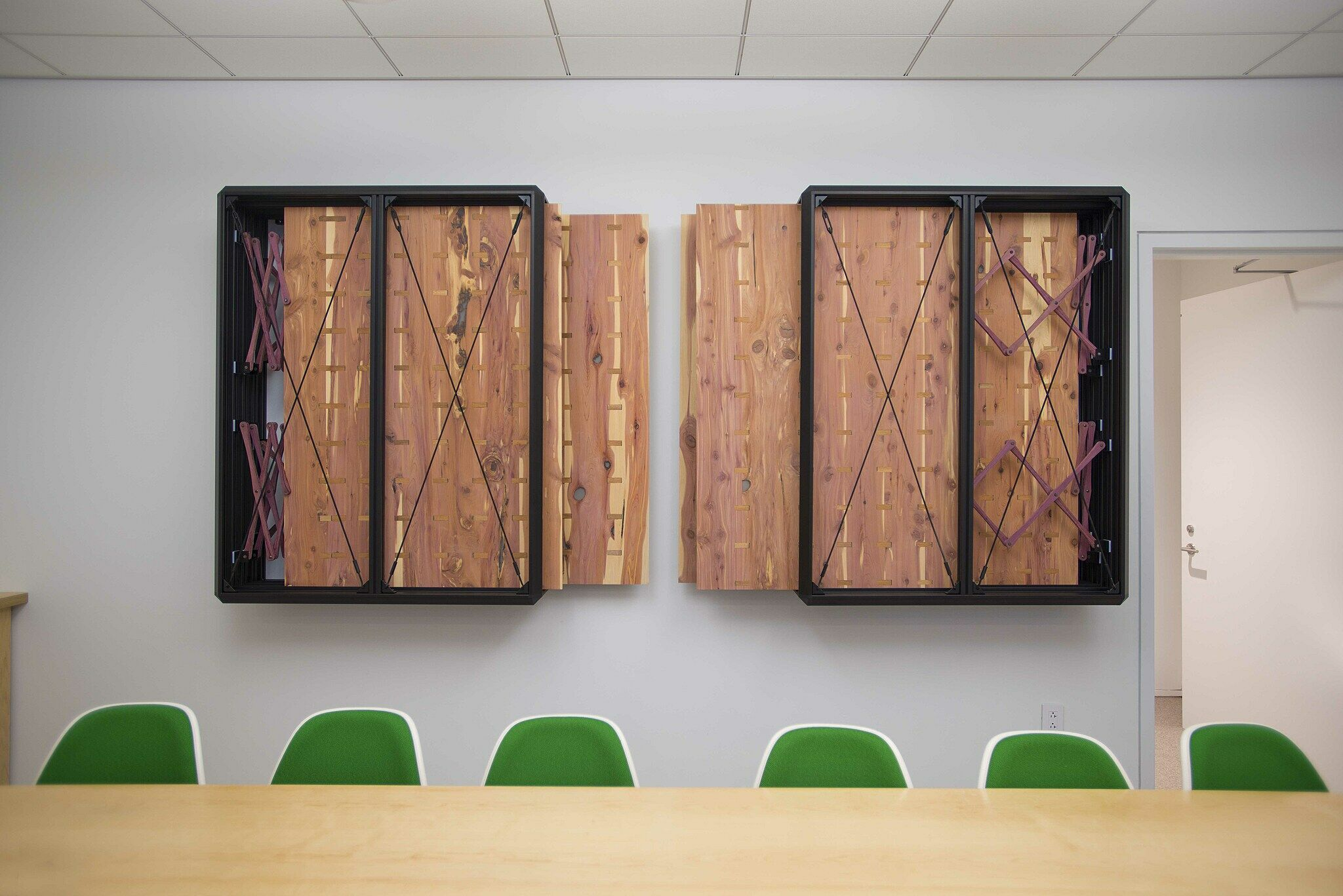 Two rectangular metal boxes containing wooden sheets, mounted on the wall of a conference room
