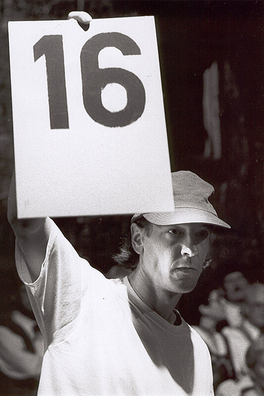 The artist Christian Marclay with a hat on holding up a piece of paper with 16 on it.