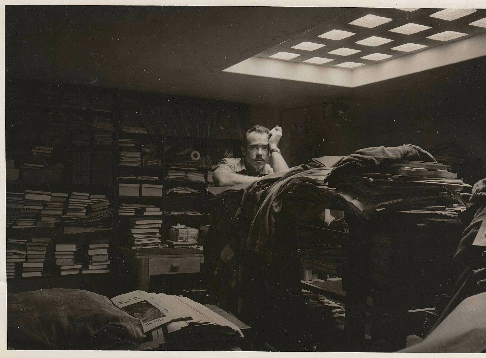 The composer Conlon Nancarrow stands amid papers and books in his library.