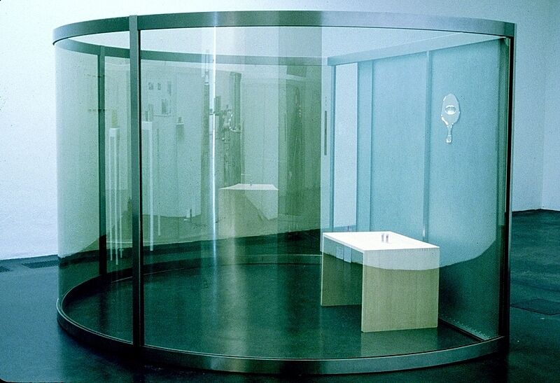 A circular glass enclosure with a table inside.