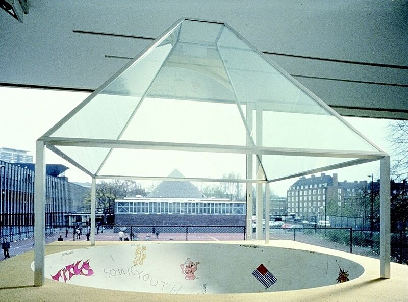 Skateboard park with a glass cover over of it.