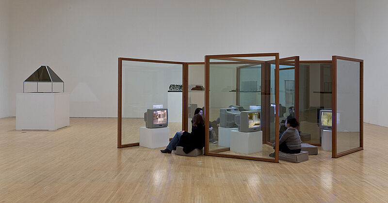Installation of Dan Graham exhibit with people sitting in front of televisions.