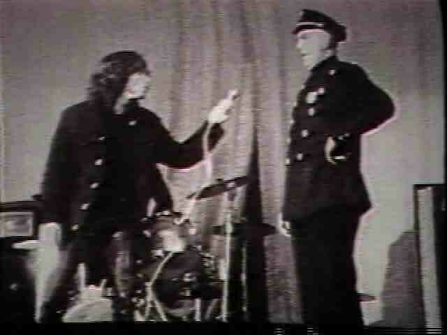 Video still of a singer pointing a microphone at a police officer on stage.