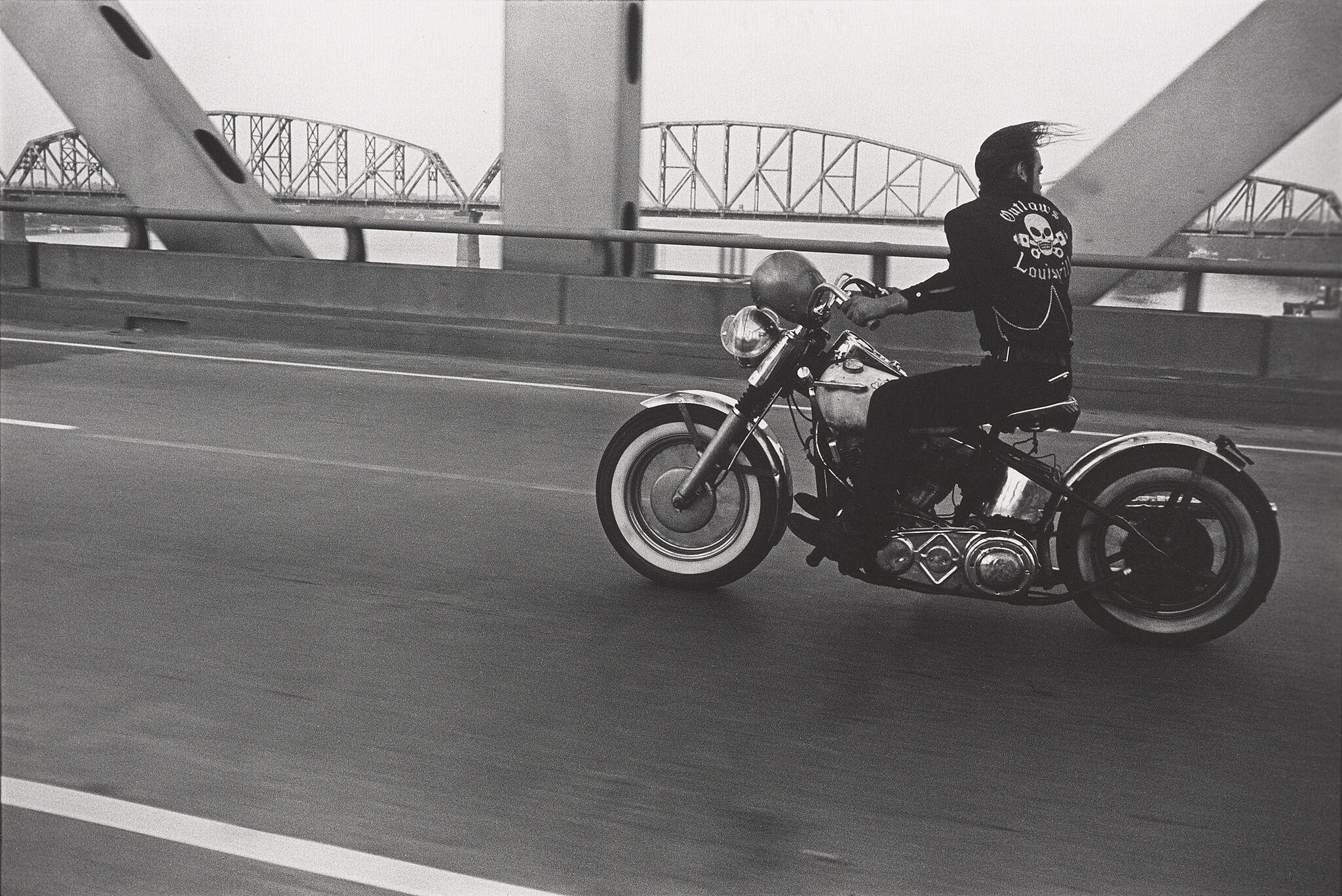 A man rides a motorcycle over a bridge.