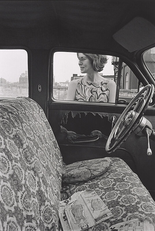 The interior of a car with a woman standing right outside the driver's seat window.