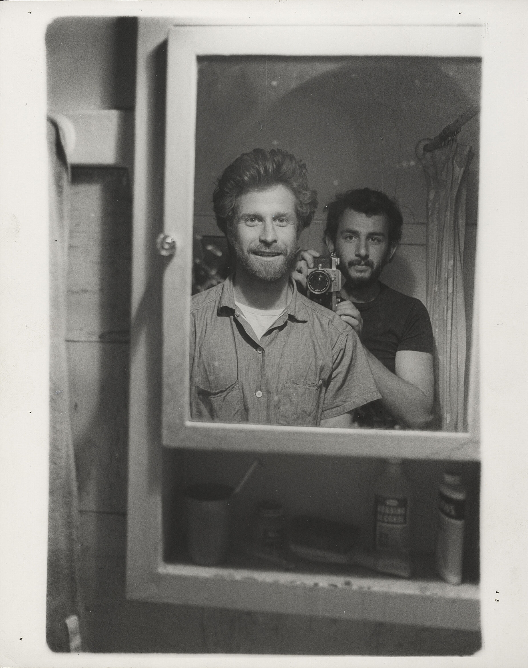 Two men looking into a mirror, one holding a camera.