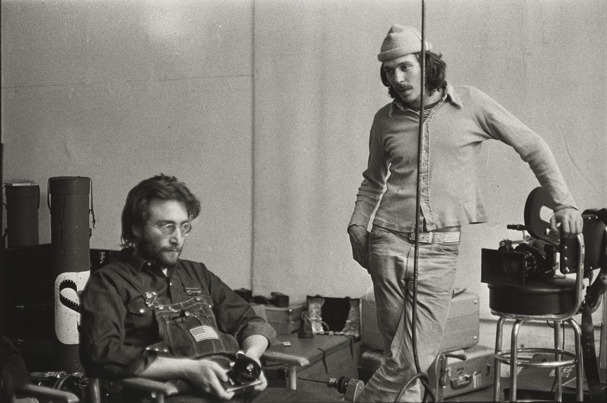 John Lennon sits in a chair and holds a camera while another man stands next to him.