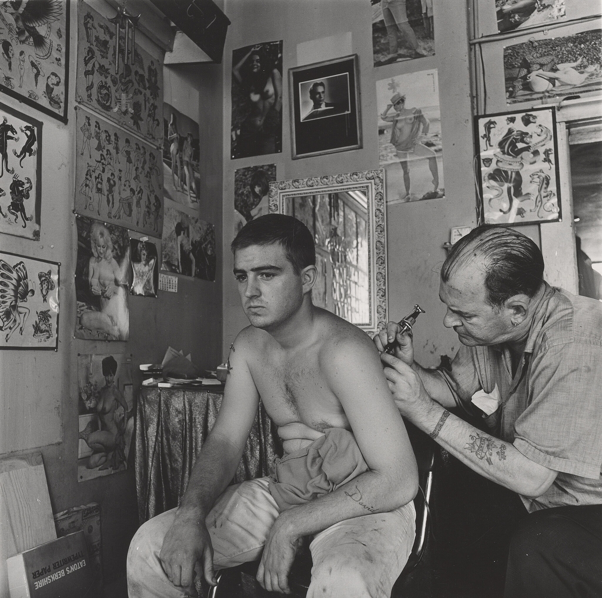 A man without a shirt gets a tattoo in a tattoo parlor.