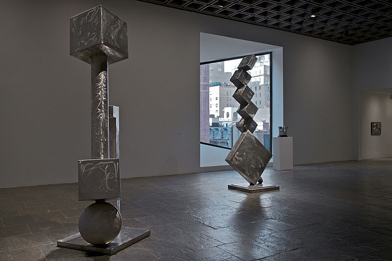 Two cube sculptures made of out of silver-colored material stand tall in a gallery.