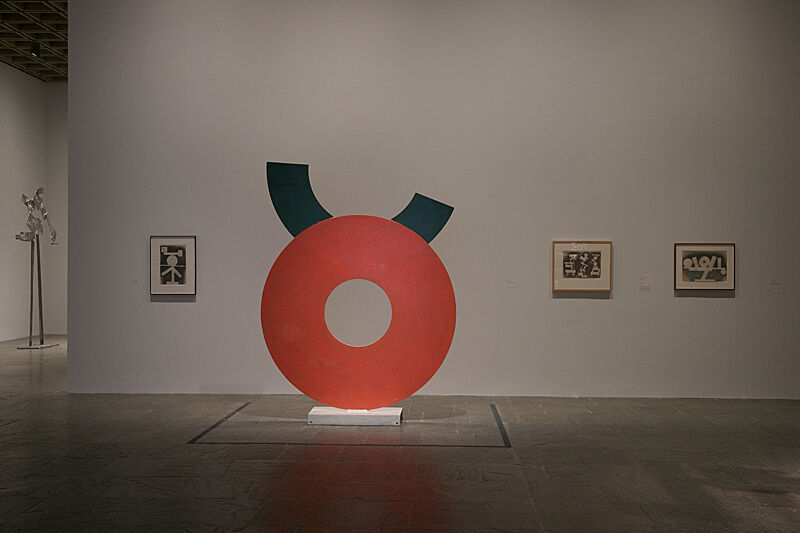 An orange and green circular sculpture in a gallery with three painting on the wall.