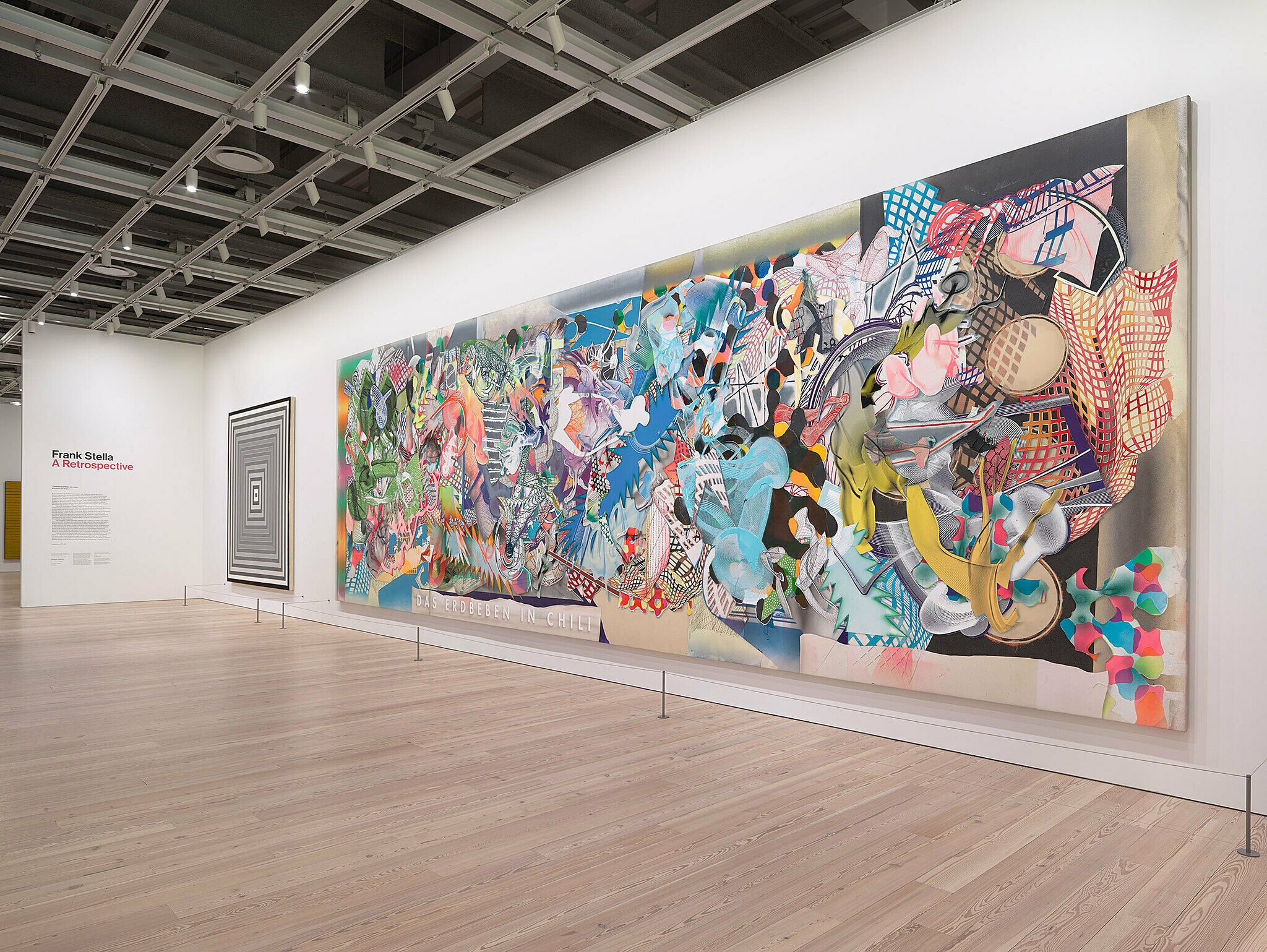A large painting covers an entire wall of an exhibition.