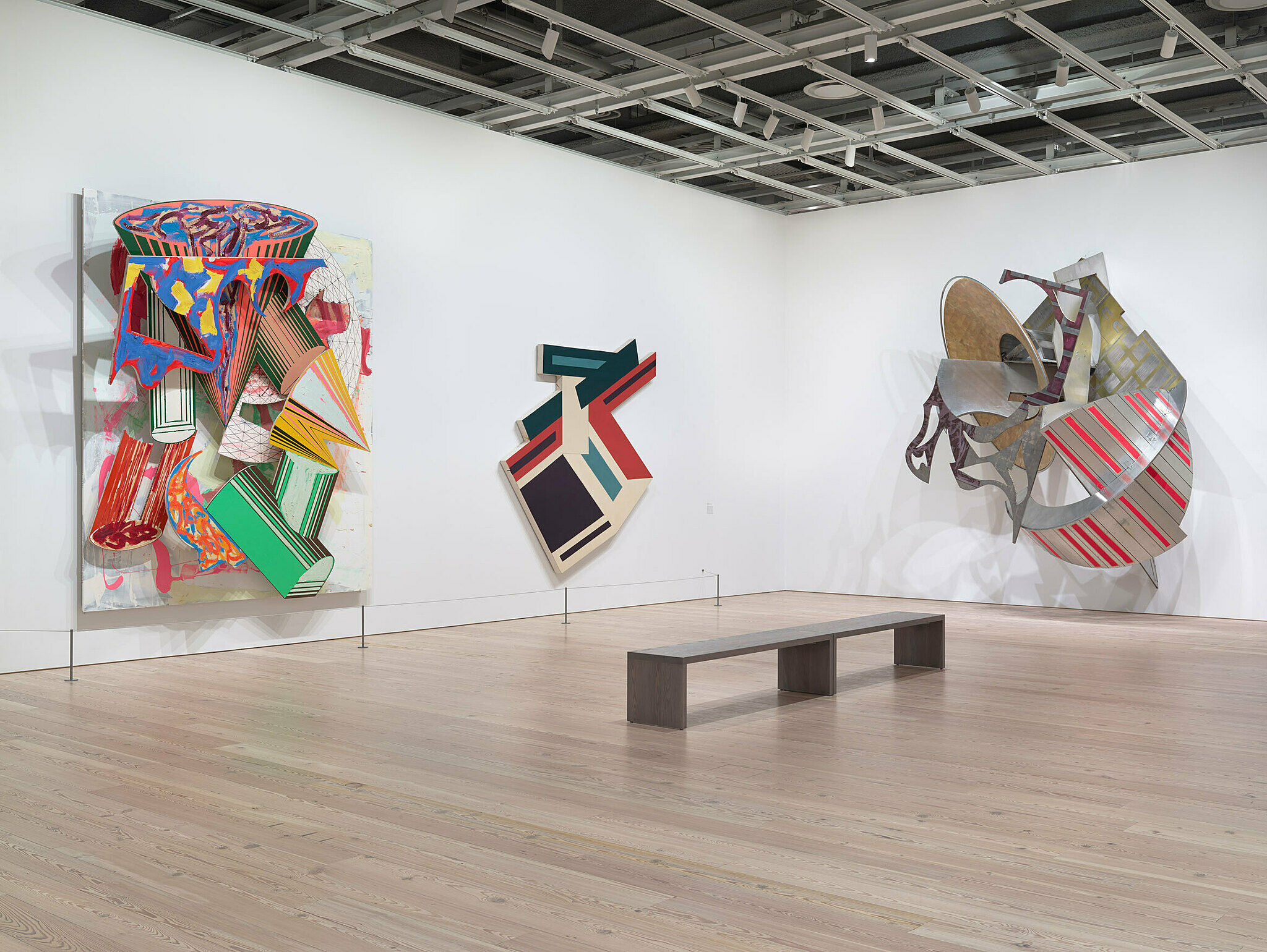 Three large abstract paintings line the walls of the exhibit.