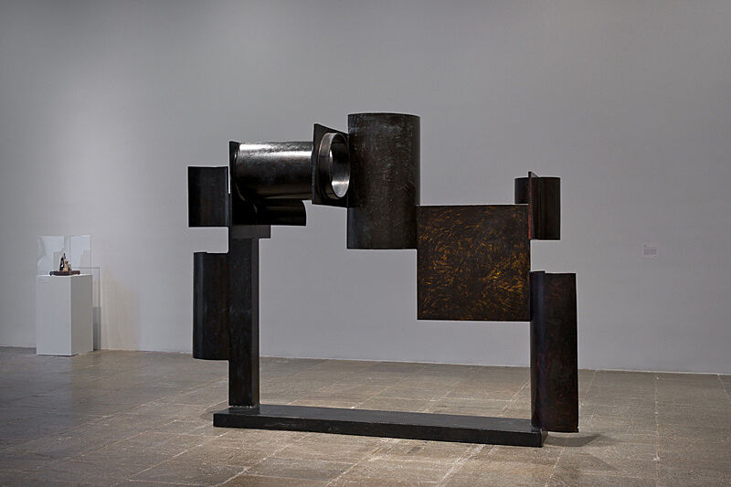 A large-scale sculpture by David Smith stands in a gallery.