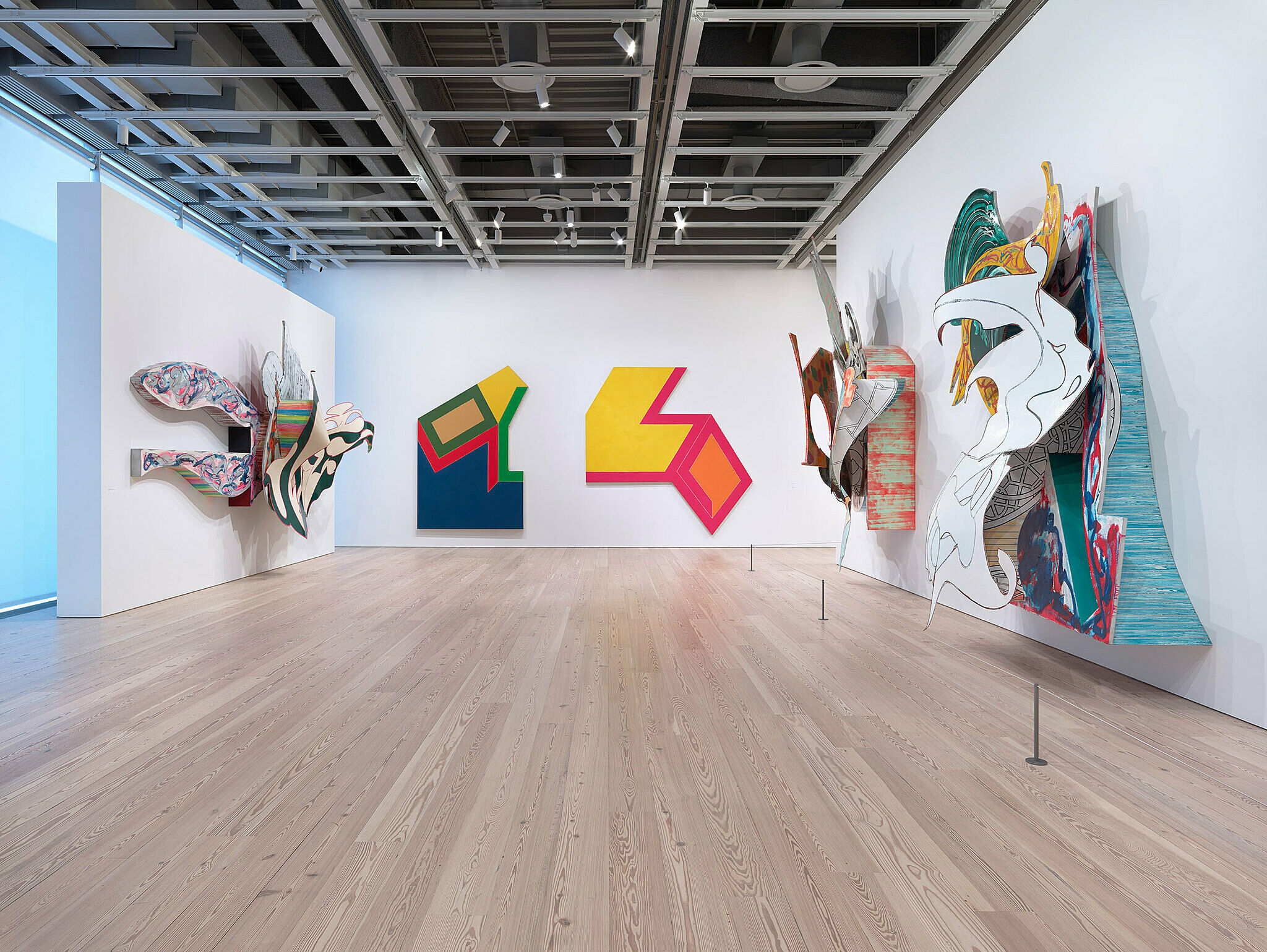 Five colorful sculptures line the walls of the gallery.