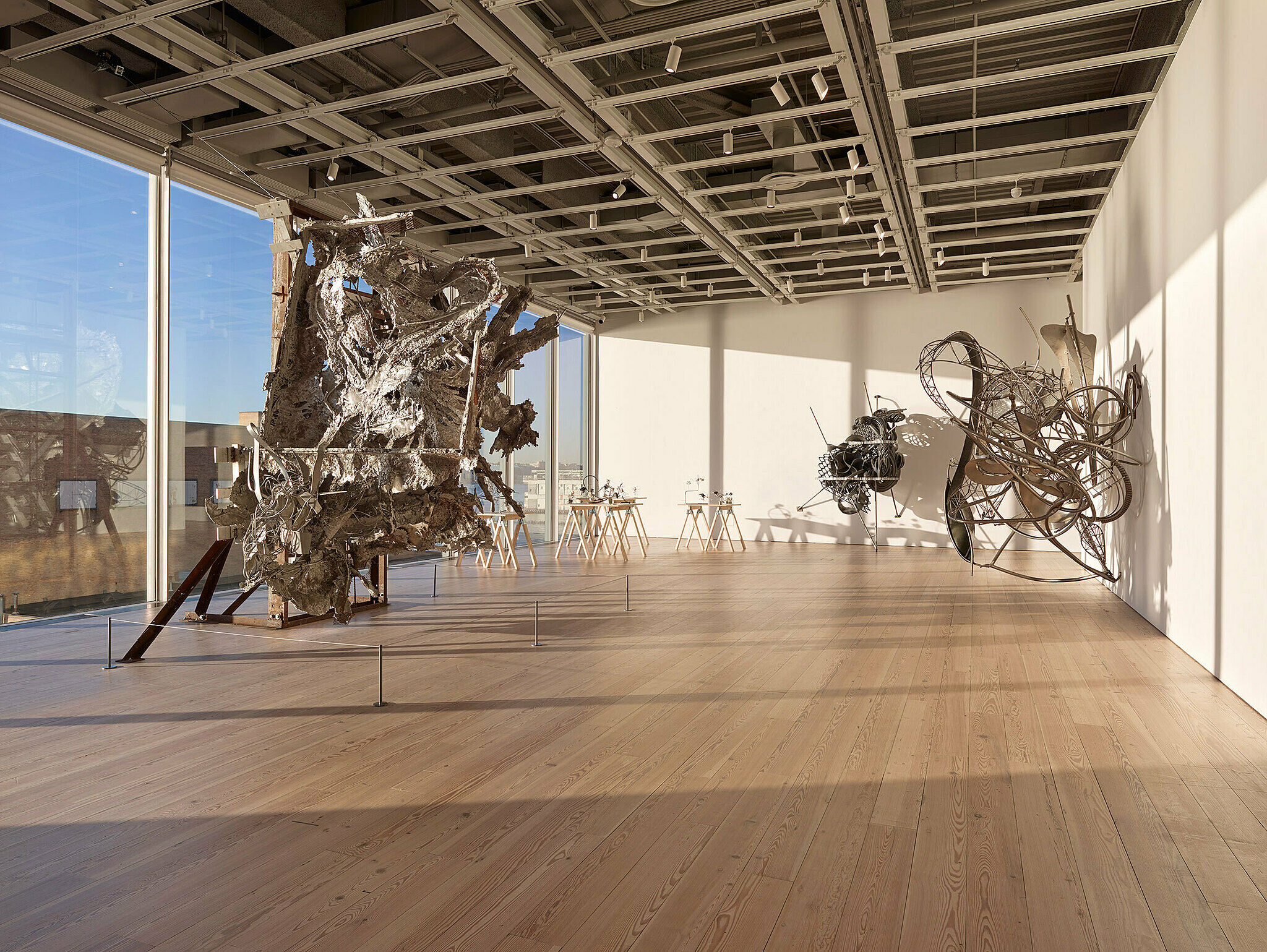 Metal sculptures hang and stand freely in a gallery space.