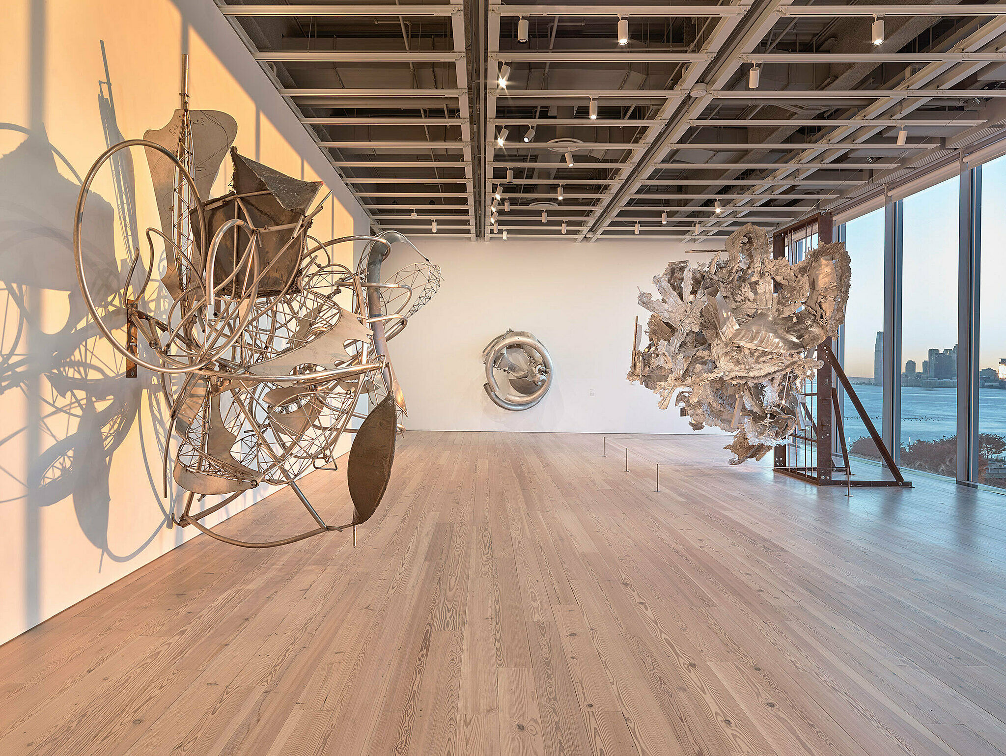 Multiple metal sculptures hang on walls and stand freely with window to the right.