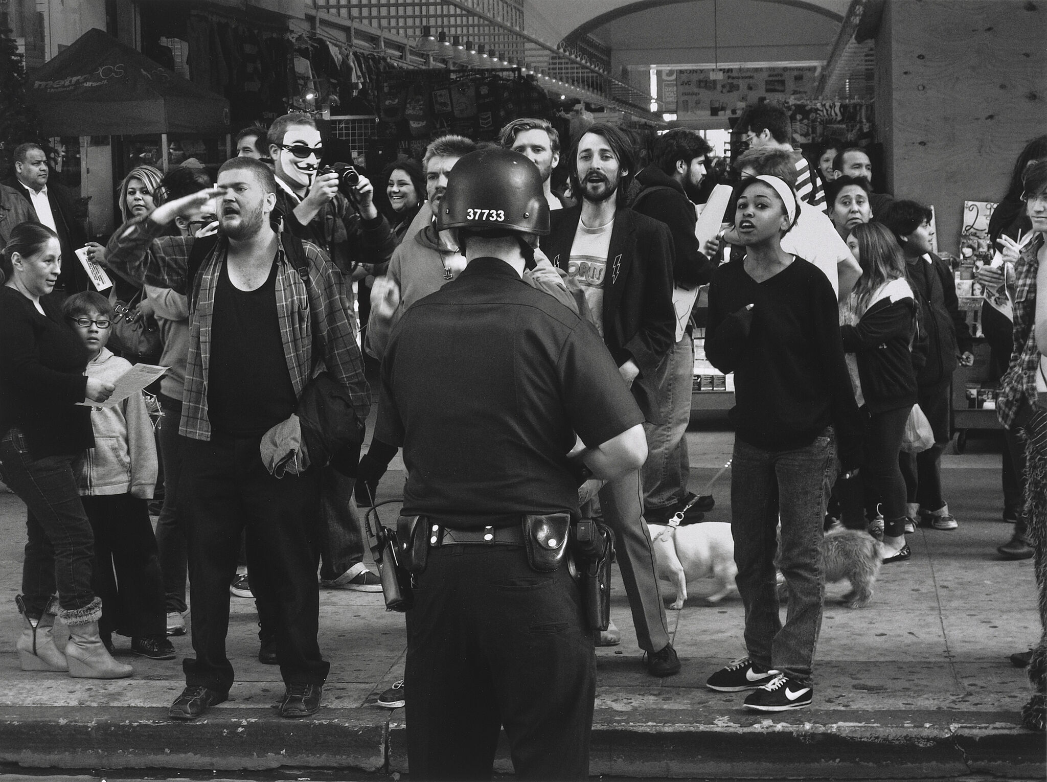 A cop with his back to the camera faces a group of young protesters on the street.