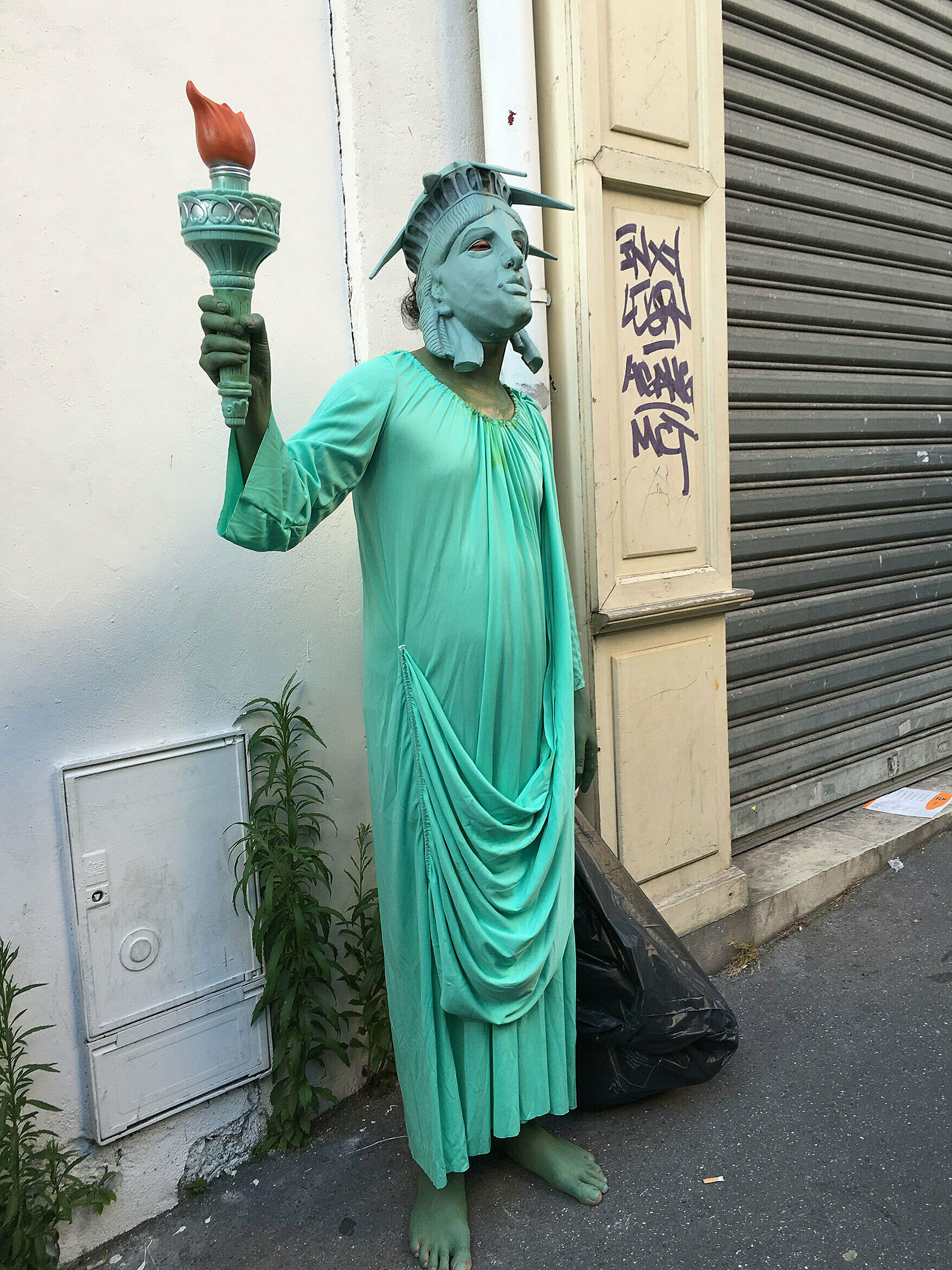 artist dressed as statue of liberty holding garbage bag