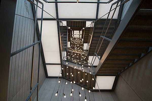 Strings of lightbulbs hanging from top of open staircase