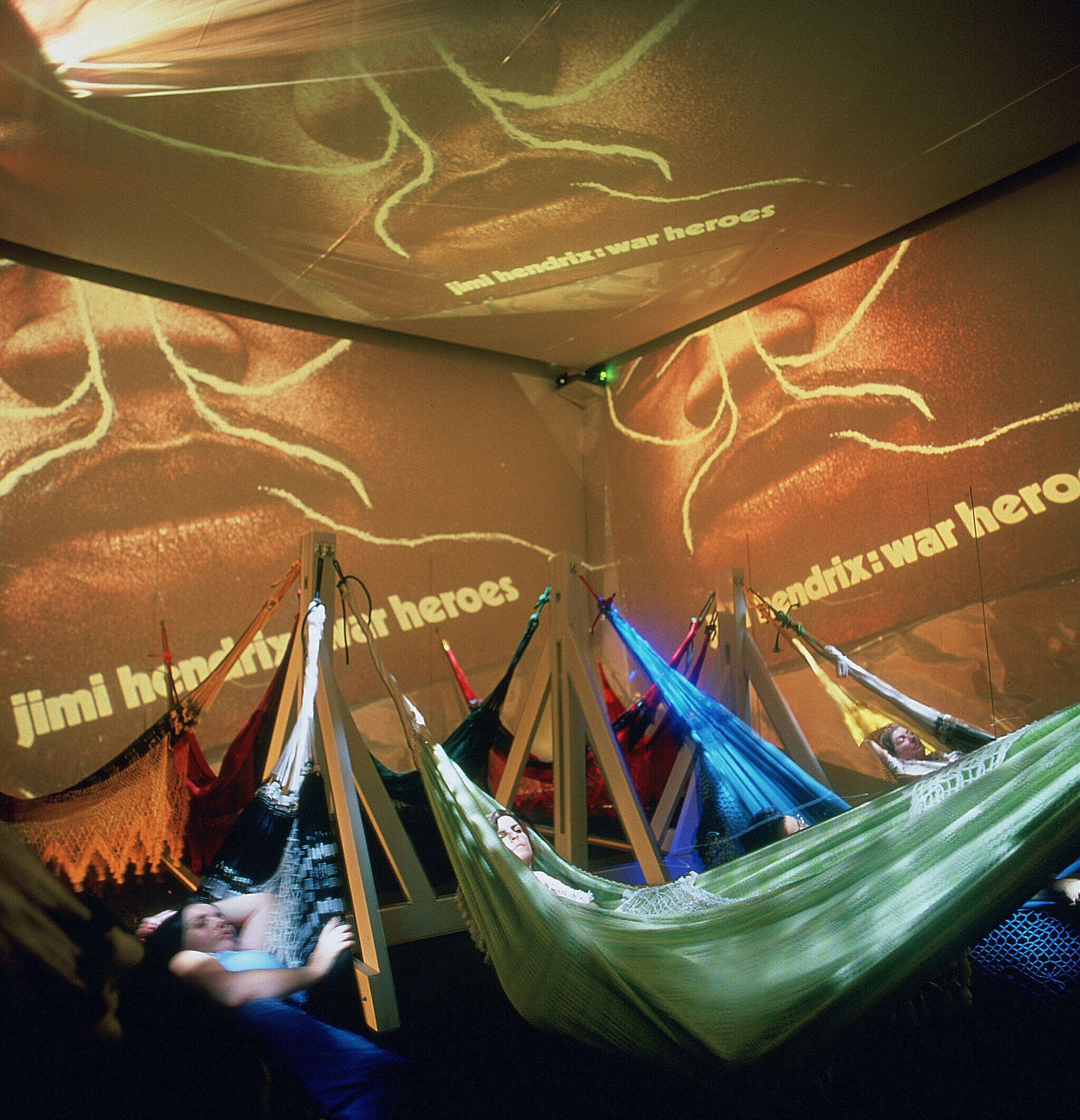 projected images on walls surrounding people in hammocks