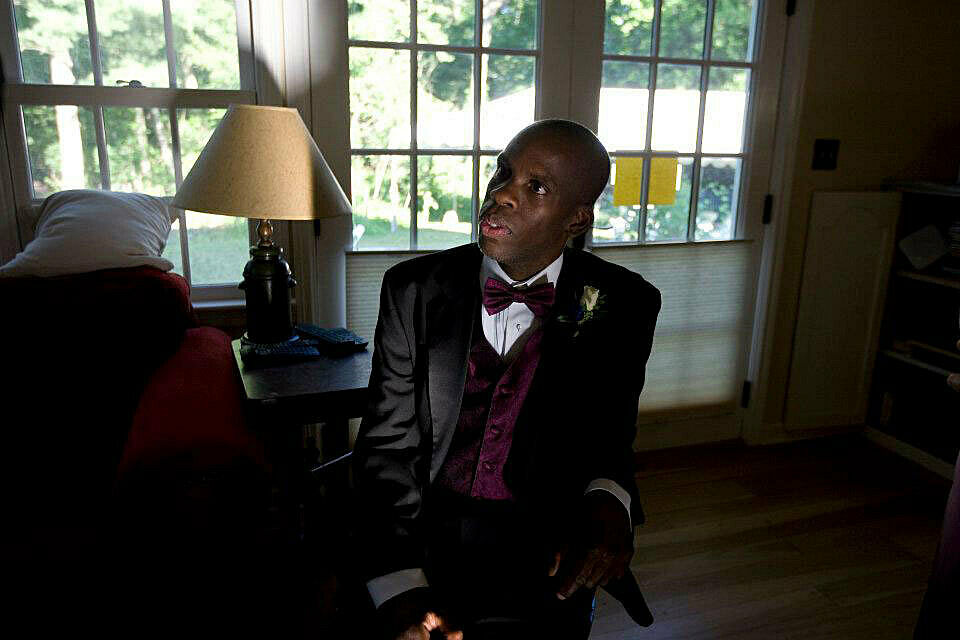 Image of Leroy Moore in a  sitting room, with a sofa table and lamp to his left and french doors in the background directly behind him, dressed in a black tuxedo with plum colored matching vest and bow tie looking left towards a speaker outside of the pi