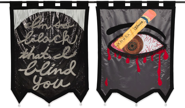 "Two banners. One that reads ""I'm so black that I blind you,"" and another depicting a pencil stabbing an eye."