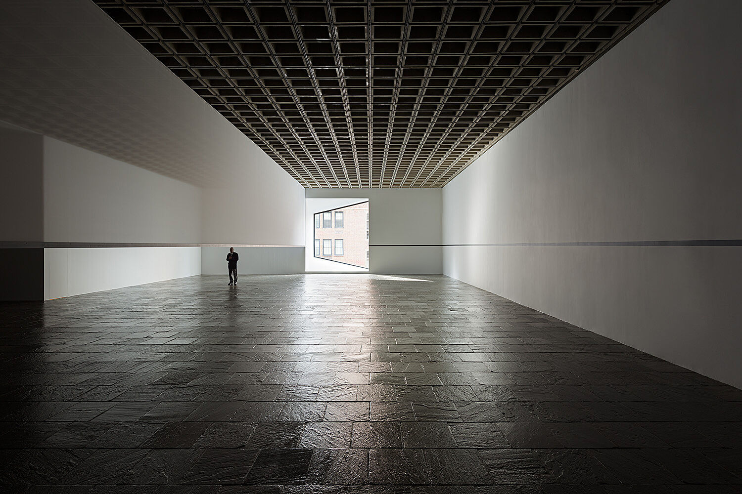 A single person stands at the end of a gallery near a window with light streaming through.