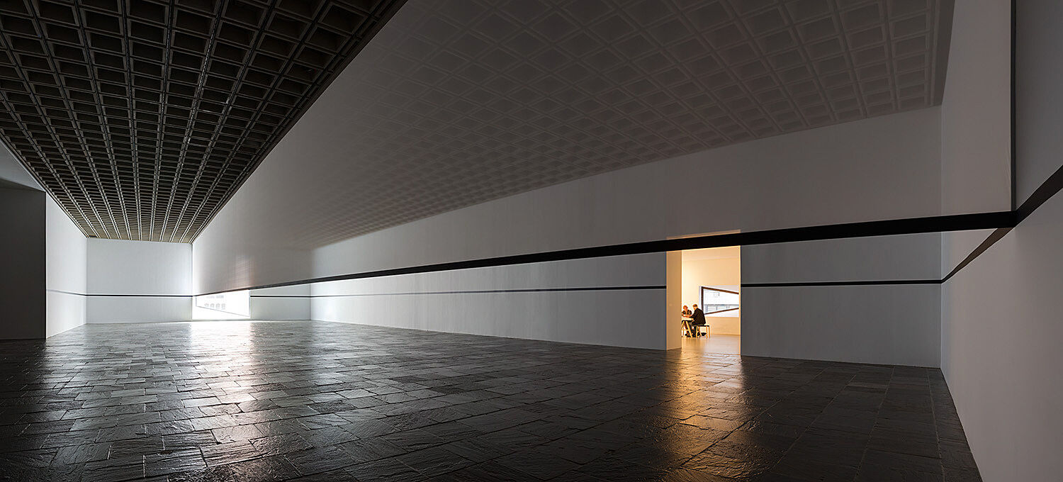 A long view of a gallery with a door to another room emanating light.
