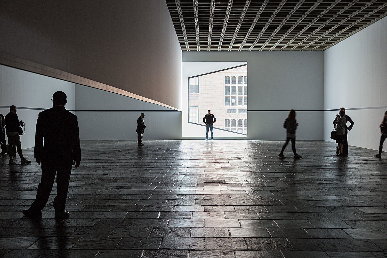 A person stands in front of a window while others stand in the gallery.