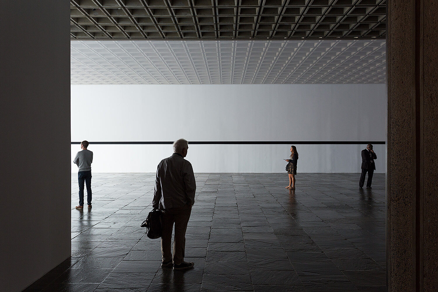 The back of a man and three other people standing in the gallery.