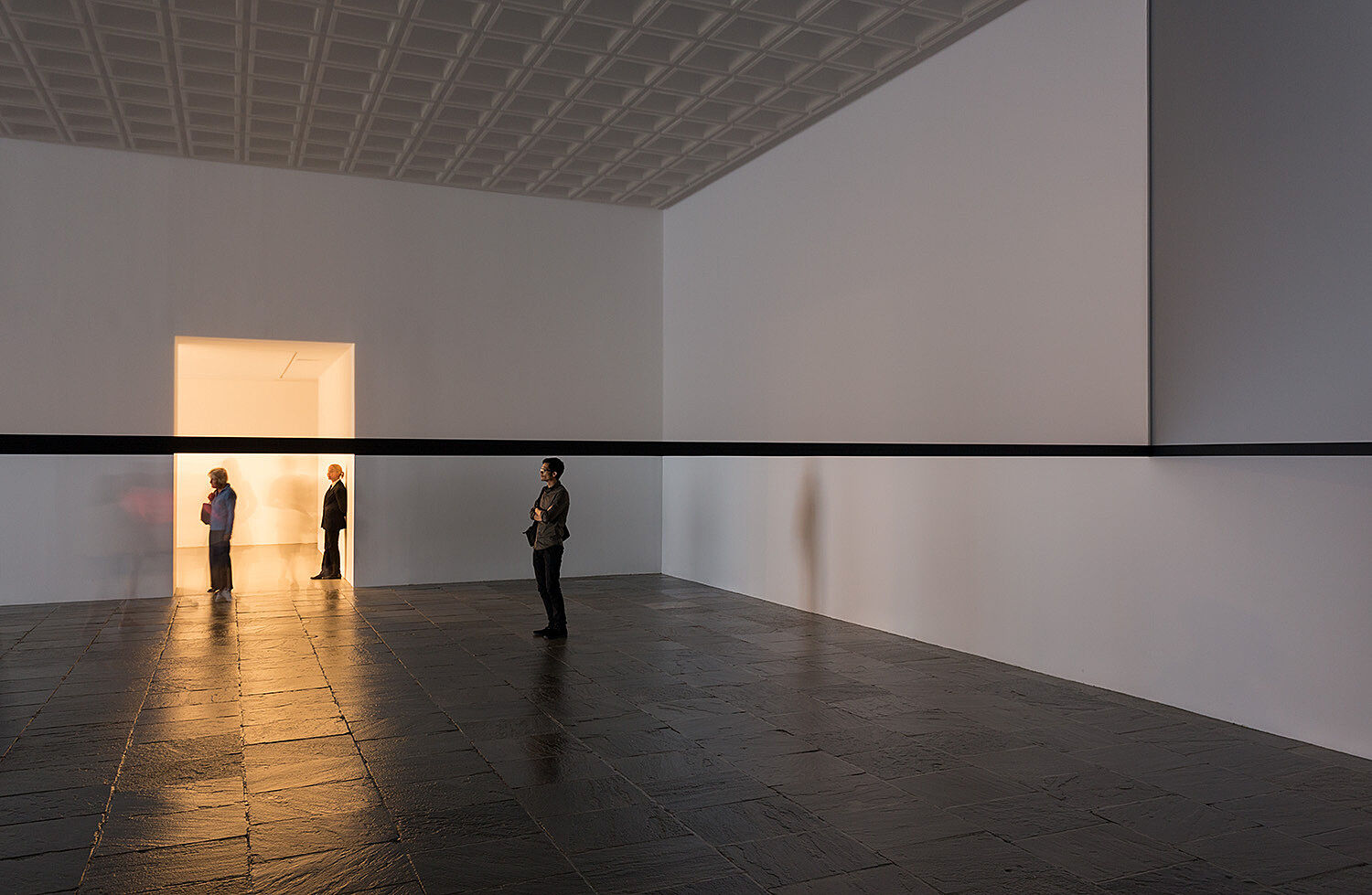 Three people in a gallery with light streaming through a door.