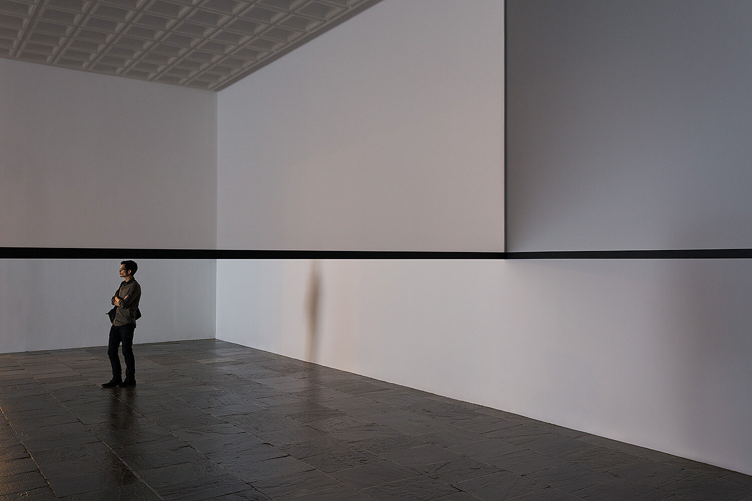 A person stands in a gallery.