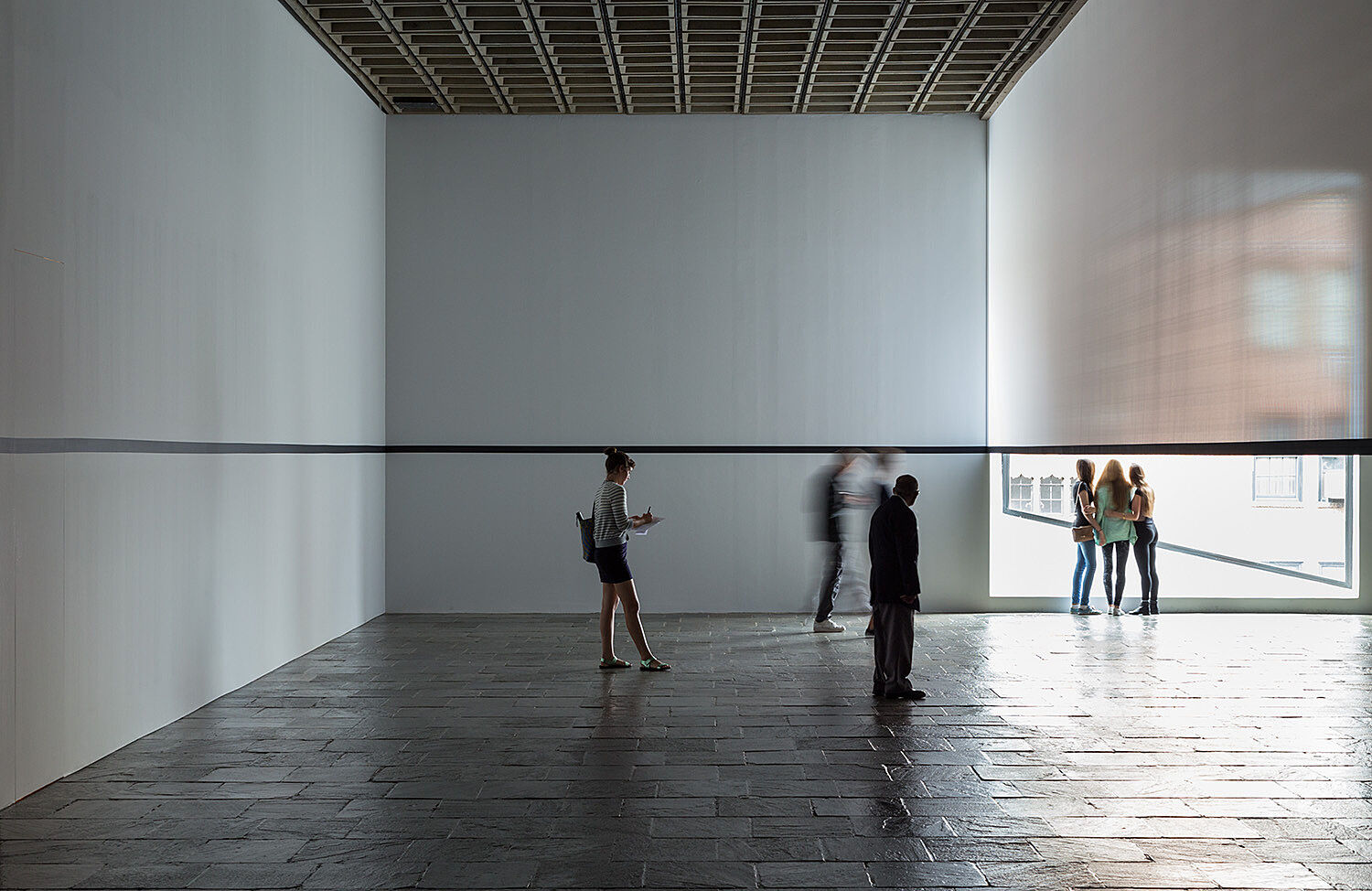 People standing in a gallery and three people looking out a window.